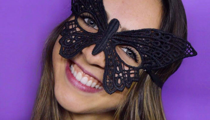 Act Attack teacher Marcela Variani wears a mask and smiles. She has long brown hair and blue eyes. Background: violet wall